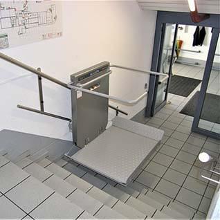 Ein Treppenlift mit Plattform für Rollstuhlfahrer über einer graden Treppe