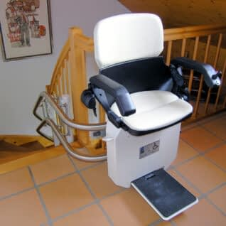 Ein Treppensitzlift als Innenläufer ausgeführt über einer Holztreppe im Innenbereich