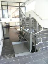 Der Plattformlift einseitig offen auf der zweiten Zwischenetage (Schulhaus)