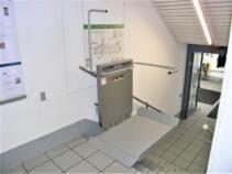 Der Treppenlift an der oberen Haltestelle, einseitig offen für Rollstuhlfahrer