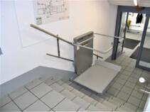 Der Rollstuhllift während der Fahrt über die kurze gerade Eingangstreppe