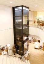 Senkrecht-Plattformlift in Möbelhaus über zwei Etagen mit verglastem Liftschacht
