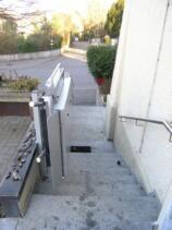 Ein Plattformlift im Aussenbereich über eine längere Zugangstreppe