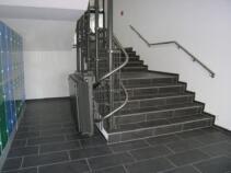 Ein Rollstuhl-Treppenlift in einem Schulhaus über mehrer Stockwerke zusammengeklappt unten