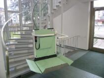 Ein Plattformlift über eine Treppe mit Kurve in einem Bürogebäude