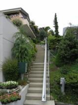 Ein Sitzlift im Aussenbereich, über eine lange Gartentreppe für barrierefreien Hauszugang